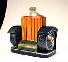 1926 Marcel Guerlain Rolls Royce perfume bottle and stopper, clear/frost glass, presented on stand of celluloid, Bakelite, pearl, and wood. Bottle 3 1/4 in.