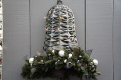 Mooie kerstklok tegen de muur, gevlochten met fietsbanden en opgemaakt met kerstgroen.