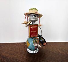 Assemblage Art Robot - Carmen is ready for her world tour, and feels like shes on top of the world! First stop, Central America. Her friends gave her this awesomely campy hat as a going away gift, and Carmen loves it! She carries her Grandfathers suitcase.