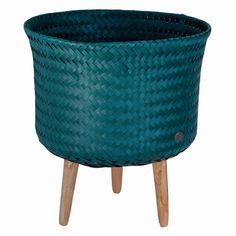 Pleciony kosz w kolorze niebiesko-zielonym na trzech drewnianych nogach to oryginalny pomysły na dekoracje wnętrza w stylu jungle. Dzięki niewielkim rozmiarom idealnie sprawdzi się jako stylowa osłonka na doniczkę w każdym małym salonie.