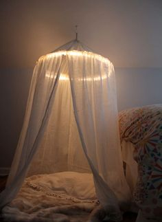 The curtains (you could also use top sheets) will probably be over $1, but they'll still be super cheap at the dollar store. And you can skip the lights to cut down on the cost. Get the full tutorial here.