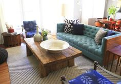 wooden table and teal tufted sofa