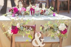 Sweethearts' table decorated with berry and white flowers along backs of wooden folding chairs and a gold ampersand.