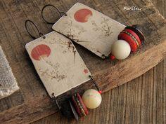 * * * Soleil rouge * * * Ces boucles doreille sont montées sur un fermoir en cuivre patiné. Ensuite un pendentif en cuivre au motif asiatique destampe japonaise, une perle tibétaine en os de yak, une coupelle, une perle en pierre de lave, une perle de rocaille et une perle en amazonite