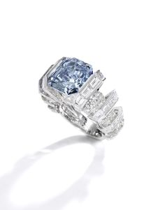 'THE SKY BLUE DIAMOND' Superb fancy vivid blue diamond ring, Cartier Set with a square-cut fancy vivid blue diamond weighing 8.01 carats, the geometric mount set with brilliant-cut and baguette diamonds, size 51, signed Cartier, numbered, French assay and maker's marks.