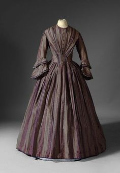 Dress 1845-1850  Silk and cotton mainly purple and gray with a boned bodice adorned with a row of buttons. Hook closure in the back and ruffled cuffs.