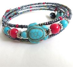 This memory wire wrap bracelet features a Turquoise Magnesite stone carved in the shape of a turtle. There are Red Coralbeadsand square blue Magnesite stones. The red and the blue represent Mother and Memory Wire Jewelry, Memory Wire Bracelets, Ankle Bracelets, Wire Wrapped Jewelry, Beaded Bracelets, Beaded Jewelry Designs, Jewelry Patterns, Bracelet Designs, Necklace Designs