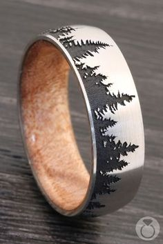 Intricately crafted, this laser etched, comfort-fit men's band carefully depicts the mystique and beauty of forestry across blackout satin finished Cobalt Chrome, while incorporating an inner sleeve of Boxelder Burl wood. Proudly made in the USA. Cool Wedding Rings, Gold Engagement Rings, Cluster Ring, Wedding Men, Wedding Bands For Men, Tree Wedding, Unique Rings, Gold Rings, Rings For Men