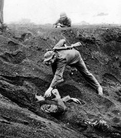 "greasegunburgers: "" A Marine gives a Japanese Soldier a cigarette after discovering the soldier had buried himself and played dead for nearly two days, Iwo Jima, Japan, 1945. """