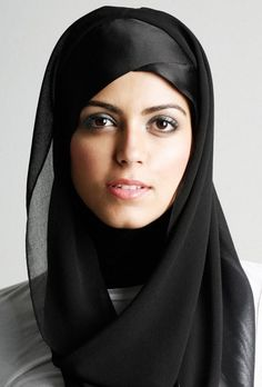 This is a Muslim woman wearing a hijab. This is a typical form of Muslim religious dress for women. The women choose to cover themselves as a way of showing their faith to their God. This style of dress is very middle Eastern, and not seen as a typical style of Western Dress.
