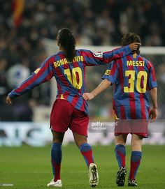 Ronaldinho (L) of Barcelona celebrates with Lionel Messi after scoring a goal during the Primera Liga match between Real Madrid and F.C. Barcelona at the Bernabeu on November 19, 2005 in Madrid, Spain.