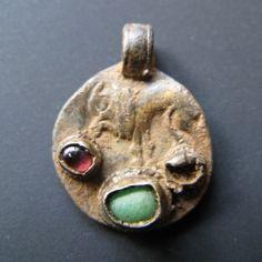 An Anglo-Saxon period pendant made from a silver Roman coin. Circa 8th century.
