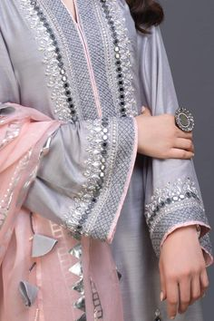 """Afsanah"" is a revival of the traditional artisan work. A pure kataan silk ,opal grey shirt  adorned with handcrafted sheesha work, aari, gota , kora dabka and pearls. with pure blush pink cotton silk, screen printed, hand hemmed finishing to enhance the shirt. For a more richer look, it is paired with a blush pink , p"