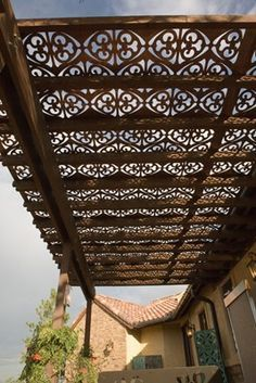 Decorative metal sheets added to a pergola lend a Moroccan vibe to this patio.