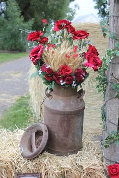 country wedding decor - milkcan with roses and wheat This is hideous but could be cute...the potential is there!! I would love to see this with wheat and lavender with a large floppy burlap bow :)