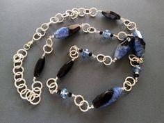Collana Chanel composta da onice, agata blu e nera e cristalli, montata con componenti e catena in metallo color argento. Realizzazione artigianale.