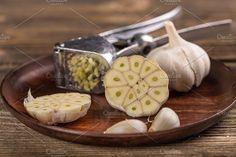 #Half garlic  Half garlic and garlic press in wooden plate