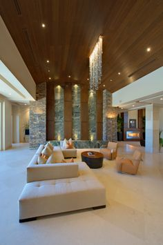 Spectacular living room with cathedral wood ceiling, S-shaped sectional, unique focus wall and ambient and direct lighting including a waterfall light.