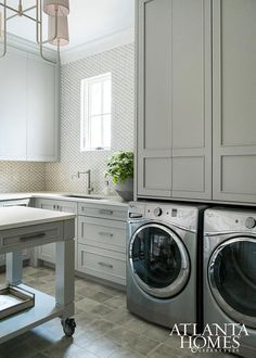 Contemporary gray laundry room features gray cabinets paired with Cambria quartz countertops fitted with a stainless steel sink and modern faucet.