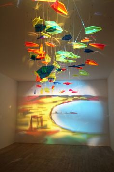 Artist Rashad Alakbarov from Azerbaijan uses suspended translucent objects and other found materials to create light and shadow paintings on walls. This painting, made with an array of colored airplanes, is on view at the Fly to Baku exhibition at De Pury Gallery in London