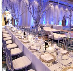 """reception was designed to look like a """"winter wonderland,"""" with all-white decor and the white walls uplit in blue. Six-foot-tall centerpieces of silver branches completed the dramatic decor."""