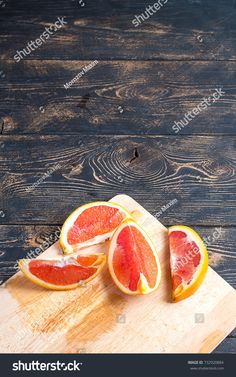 Slices of red orange light lay on a bamboo cutting board. Dark brown wooden background.