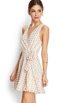 A femme piece, this sleeveless wrap dress features a ditsy floral print and self-tie waist. Compl...