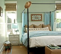 Master bedroom has the beachy colors, natural rug and window shades.