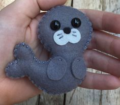 felt art This little soft wool felt seal / sea lion ornament / key chain is an original design by myself which is hand cut, sewn and stuffed with cotton. Keep in mind the picture listed above Easy Felt Crafts, Felt Diy, Felt Christmas Ornaments, Diy Christmas Gifts, Kids Christmas, Baby Mobile Felt, Felt Decorations, Felt Patterns, Embroidery Patterns