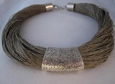 Collar diseño hilos de lino natural y pieza metalica grabada. Color plata fantasia .