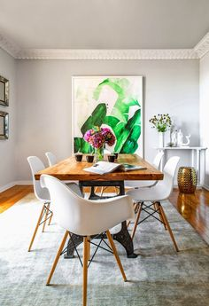 A modern dining space with eye-catching green art, flowers as centerpiece and white chairs