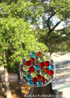 EASY Dollar store SUN CATCHERS!!!    ■Plastic container lid   ■Clear Elmer's Glue (cloudy will work too, but will dry a little opaque)   ■String or Thread   ■Suction cup window hooks (optional- you can just tie the string to the window latch instead)   ■Glass vase gems