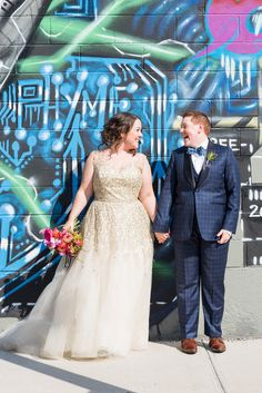 Gay wedding at 501 Union in Brooklyn, New York with graffiti wall pics of the brides. Photos by NYC wedding photographer, Mikkel Paige Photography.