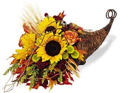 Harvest Cornucopia Floral Bouquet:  This breathtaking array of fall colors and textures is enough to take anyones breath away. As a Thanksgiving centerpiece or decoration, the cornucopia's abundance symbolizes the fullness of our lives. Sunflowers, roses, mini carnations, solidago, wheat, and fall leaves arrive in a wicker cornucopia.