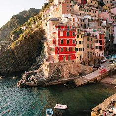 """We sat here with our feet dangling off the promenade, gelato in hand, as we watched the sun go down over the sea. The old men in the fishing boats ignored us, intent on tying up their tiny ships, bringing the day's catch to shore, and racing home."" -@simone anne Riomaggiore, Cinque Terre, Italy #passionpassport"