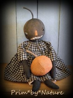 Primitive Pumpkin Doll With Pumpkin. Overall she is 17 inches tall. When sitting she is 10 inches which is just the right size for a cupboard shelf. Her pumpkin measures 4 inches tall. She is made from dyed and aged fabric. She has beaded eyes a hand-stitched nose and applied raggedy mouth. Visit me @ primbynature.com