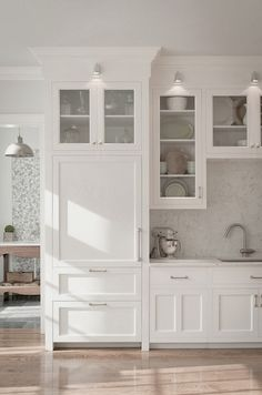 White cabinets to the ceiling, glass doors, lower drawers