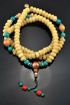 Beeswax and Turquoise Mala - Hinky Imports  This mala is made from beeswax beads. Each bead is 8 mm. This mala was handmade in Nepal. There are turquoise spacer beads on this mala. There are three turquoise and coral counting beads at the end of the mala, and the guru bead is made from copper.