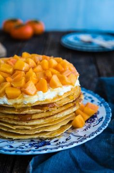 Dessert and breakfast come together and it is heavenly. Soft pancakes, layered with whipped cream and jam is drizzled with honey and topped with vibrant persimmons.