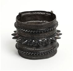Bangle Zanzibar, Tanzania 19th century Silver, with filigree decoration and bosses of cast work  Throughout history the Zanzibar archipelago has served as a staging post for Indian Ocean traders and explorers. In 1698 it became part of the overseas holdings of Oman  This hinged silver bracelet is decorated with rows of conical bosses of different sizes and bands of filigree work. A label on the bracelet notes that it was made by the natives at Zanzibar .. and brought to England