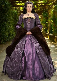 Purple Tudor style gown. Excellent fabric and trim choices. Obviously, she also took the time to use proper support garments as well so that the whole dress hangs right!