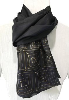 Bold, decisive and confident describe this large scarf and the men who will wear it. This large black silk scarf is constructed from two panels of 100% pure soft silk. One side is hand dyed in blue and black with the thin gold square maze design. The other side is hand dyed in gray and hand painted with Zen Stripes. This large scarf is suitable for men or women. The Zen Scarf is packaged in a sleek reusable metal gift box with care instruction included. The dimension of the box is 5.75 in…