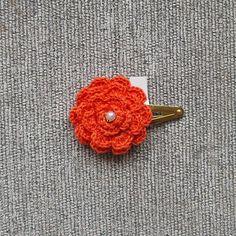 Flor em crochê com perola no prendedor modelo tic-tac.