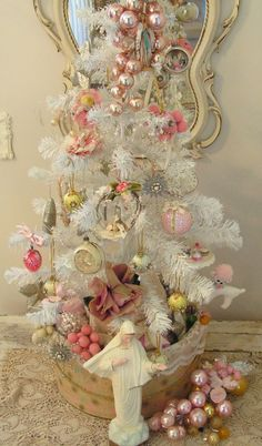 It's trimmed with little bits and pieces of vintage goodies in a palette of pink, cream, pale green & yellow. It sits on a yard-sale-find chippy old table, and I placed it in an old hatbox which was first filled with yards of lace to cover the tree base.