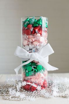 Tossing red, green, and silver-wrapped candy into a vase is festive even when they're all mixed together. But take the look to the next level by creating color-coded stripes (have kids help you separate the candies when you open the packages). For this tall vessel, we used about five standard bags of candy. Tie a bow around the center for finishing touch.  - GoodHousekeeping.com