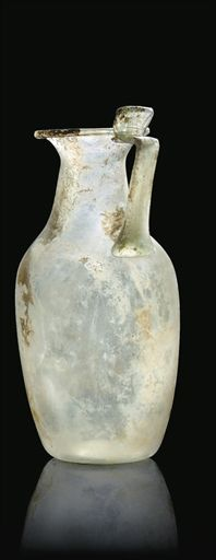 A LARGE ROMAN BLOWN CLEAR GLASS JUG 2ND CENTURY A.D. The tapering body with shallow concave base, the cylindrical neck narrowing to outward-flared rim with inward-folded lip, the applied ribbon handle with projecting folded thumbrest 10 5/8 in. (27 cm.) high