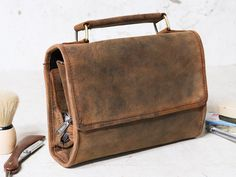 New for summer 2020. Our deluxe leather hanging washbag is perfect for those on the move. The washbag simply unrolls and hangs for easy access to all your toiletries and more - perfect for those weekends away and holidays. Handmade by our expert bag makers from the finest vintage style leather using traditional leather working tools and techniques. #accessories #giftideas #giftideasforhim #giftideasforher #christmasgiftideas