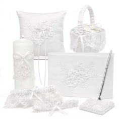Sweetly Smitten Wedding Set includes a flower girl basket, keepsake garter, toss garter, guest book, pen set, ring bearer pillow, and unity candle. Each piece features matte white satin, a mesh overlay with embroidered foliage, chiffon ribbon flowers, and sequin accents.
