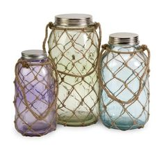 This set of three beach glass jars with closeable lids, features pastel hues of blue, green and purple with nautical inspired thin jute netting covering each jar.