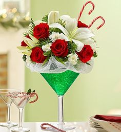 Peppermint Martini Bouquet™  Price:  US$49.99  Mix up some merry with our truly original Happy Hour arrangement of red roses, white lilies, hypericum, mini carnations and sweet candy canes. Inspired by the cool-as-ice holiday cocktail, it's gathered in an oversized martini glass to make serving up holiday smiles a snap.